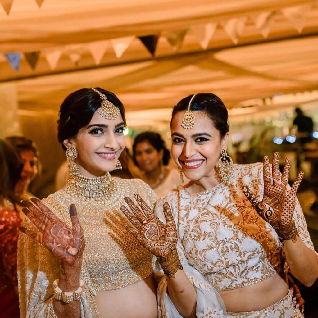 Sonam kapoor with Swara Bhaskar showing mehndi designs at a wedding